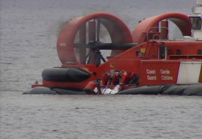 Rescue crews recover the body of one of the three crew members of the Ginga Falcon ship which arrived in Vancouver, Sunday.