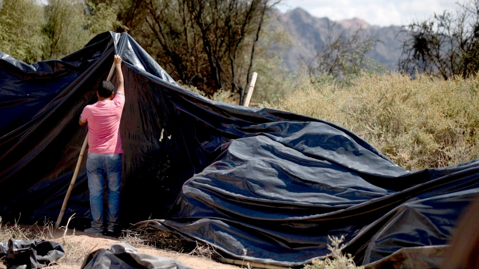 A man drapes a plastic tarp over the bodies of those killed when two helicopters crashed near Villa Castelli, La Rioja province, Argentina, Tuesday, March 10, 2015. (AP / Natacha Pisarenko)