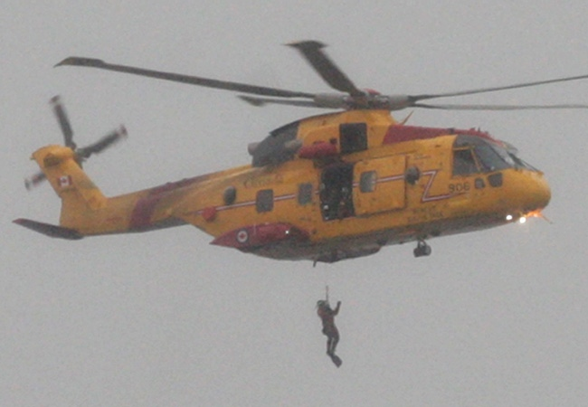 A Canadian Forces Cormorant helicopter conducts a search and rescue mission in heavy fog and rain after three Bangladeshi crew members went missing from a cargo ship on English Bay in Vancouver, B.C., on Monday, October 13, 2008. The body of one of the missing men was recovered on the waters of nearby Spanish Banks. (THE CANADIAN PRESS/Darryl Dyck)