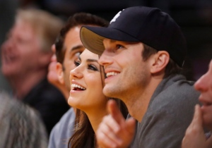 In this file photo, actress Mila Kunis, left, and actor Ashton Kutcher, right, sit courtside together at an NBA basketball game Tuesday, Feb. 12, 2013, in Los Angeles. (AP / Danny Moloshok)