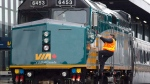 A Via Rail employee climbs aboard a locomotive at the train station in Ottawa on Monday, December 3, 2012. (Adrian Wyld / THE CANADIAN PRESS)