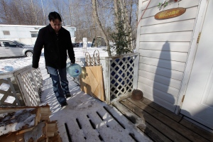 Ashley Green, a resident of Shoal Lake 40 First Nation, carries a 20-litre water container into his home Wednesday, February 25, 2015. (John Woods / THE CANADIAN PRESS)