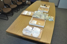 Drugs, weapons and cash seized from four homes in Cambridge and one in Ayr are seen in this photo provided by Waterloo Regional Police.