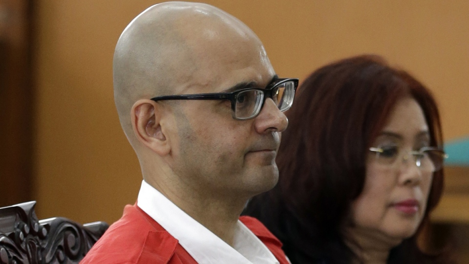 Canadian teacher Neil Bantleman, left, sits on the defendant's chair accompanied by an unidentified interpreter prior to the start of his trial hearing to listen to the prosecutor's demand at South Jakarta District Court in Jakarta, Indonesia, Thursday, March 12, 2015. (AP / Dita Alangkara)
