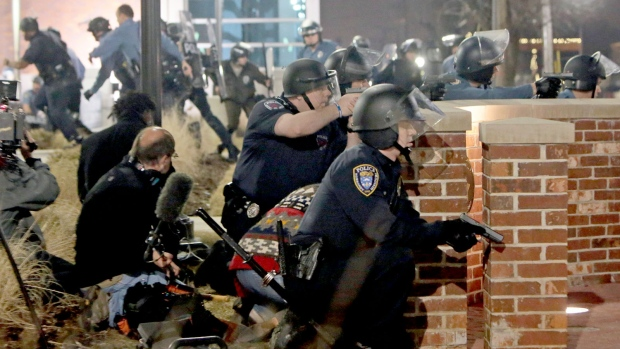 Amid resignations and allegations of racism, conflict escalated to an exchange of gunfire in Ferguson, Mo. that left two officers wounded. A hunt for suspects is now under way. <br> <br> Police take cover after two officers were shot while standing guard in front of the Ferguson Police Station on Thursday, March 12, 2015. (St. Louis Post-Dispatch / Laurie Skrivan)