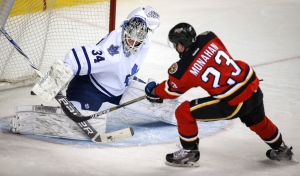Toronto Maple Leafs goalie James Reimer, left, lets in a goal by Calgary Flames Sean Monahan during first period NHL hockey action in Calgary, Friday, March 13, 2015. (Jeff McIntosh/THE CANADIAN PRESS)