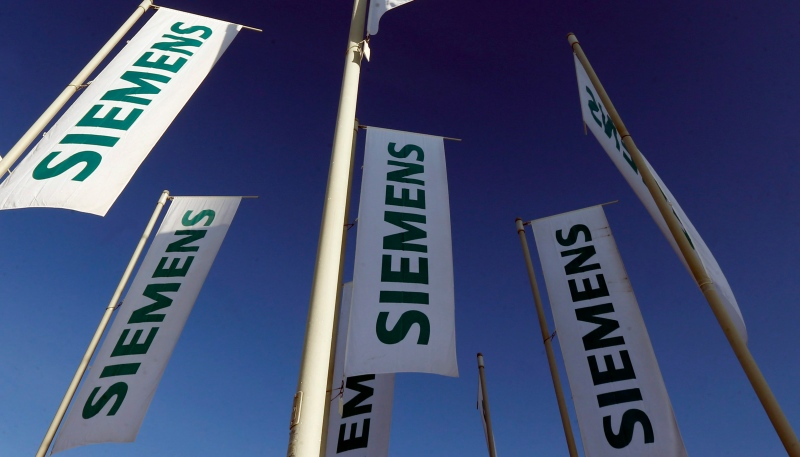 Flags of German engineering conglomerate Siemens AG flutter before the annual shareholder meeting in Munich in this Jan. 23, 2013 file photo. (AP / Matthias Schrader)