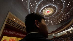 A Chinese soldier in plainclothes watches over the hall during the closing ceremony of the annual National People's Congress at the Great Hall of the People in Beijing Sunday, March 15, 2015. (AP / Andy Wong)