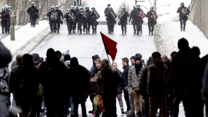 Demonstrators turn away as riot police move in during the annual anti-police brutality demo in Montreal on Sunday, March 15, 2015. (Paul Chiasson / THE CANADIAN PRESS)