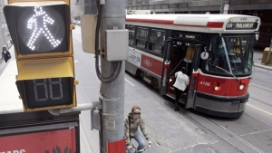 A TTC streetcar takes on passengers as a cyclist rolls past a pedestrian walk sign in downtown Toronto, Sunday, April 20, 2008. (J.P. Moczulski / The Canadian Press)