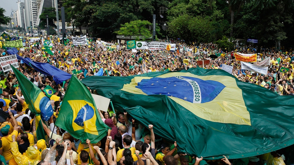 Demonstrators hold a Brazilian flag and a sign that reads in Portuguese 'Military intervention now!' during a march demanding the impeachment of Brazil's President Dilma Rousseff in Sao Paulo, Brazil, Sunday, March 15, 2015. (AP / Andre Penner)