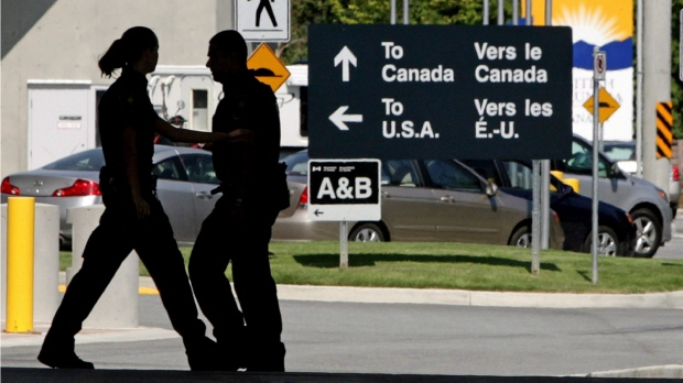 Canadian border guards are silhouetted as they replace each other at an inspection booth at the Douglas border crossing on the Canada-USA border in Surrey, B.C., on Aug. 20, 2009. (Darryl Dyck / THE CANADIAN PRESS)