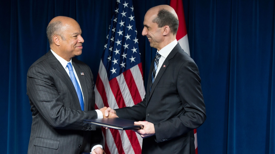 Homeland Security Secretary Jeh Johnson, left, shakes hands with Canadian Minister of Public Safety and Emergency Preparedness Steven Blaney during a ceremony in Washington, Monday, March 16, 2015, to sign a preclearance agreement as part of the Beyond the Border Initiative. (AP / Evan Vucci)