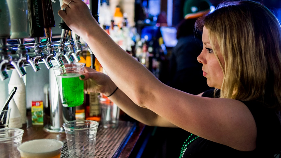 A bartender pours a green beer from the tap on St. Patrick's Day in Flint, Mich., on Tuesday, March 17, 2015. (AP Photo/The Flint Journal-MLive.com, Jake May)