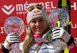 Lindsey Vonn of the United States holds the alpine ski women's World Cup super-G and downhill trophies as she celebrates on the podium, at the World Cup finals in Meribel, France, Thursday, March 19, 2015. (AP / Armando Trovati)
