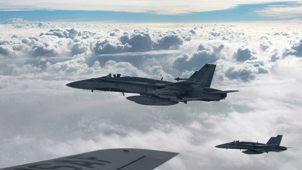 Royal Canadian Air Force CF-18 Hornets depart after refueling with a KC-135 Stratotanker assigned to the 340th Expeditionary Air Refueling Squadron, over Iraq, Thursday, on Oct. 30, 2014. (U.S. Air Force / Staff Sgt. Perry Aston)