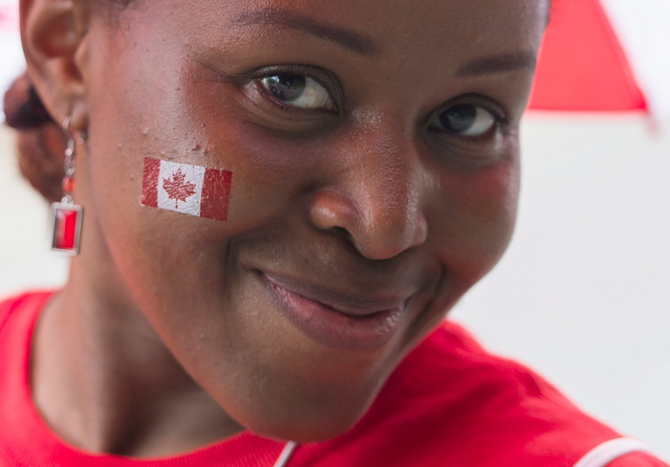 A woman enjoys the festivities during the annual Canada Day parade in Montreal, Tuesday, July 1, 2014. (Graham Hughes / THE CANADIAN PRESS)