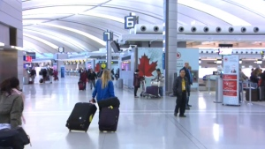 Travellers walk through Pearson International Airport in Toronto on Friday, March 20, 2015.