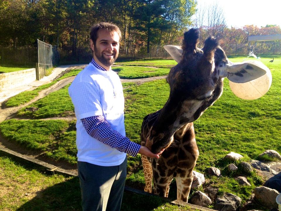 ZooShare executive director Daniel Bida is shown with a giraffe at the Toronto Zoo. (ZooShare)