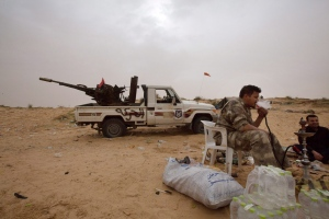 In this Saturday, Feb. 21, 2015 photo, Libyan soldiers take a break from fighting with militants on the frontline in Al Ajaylat, 120 kilometers west of Tripoli, Libya. Army forces in Libya have been fighting Islamic and tribal militias since last September. (AP/Mohamed Ben Khalifa)