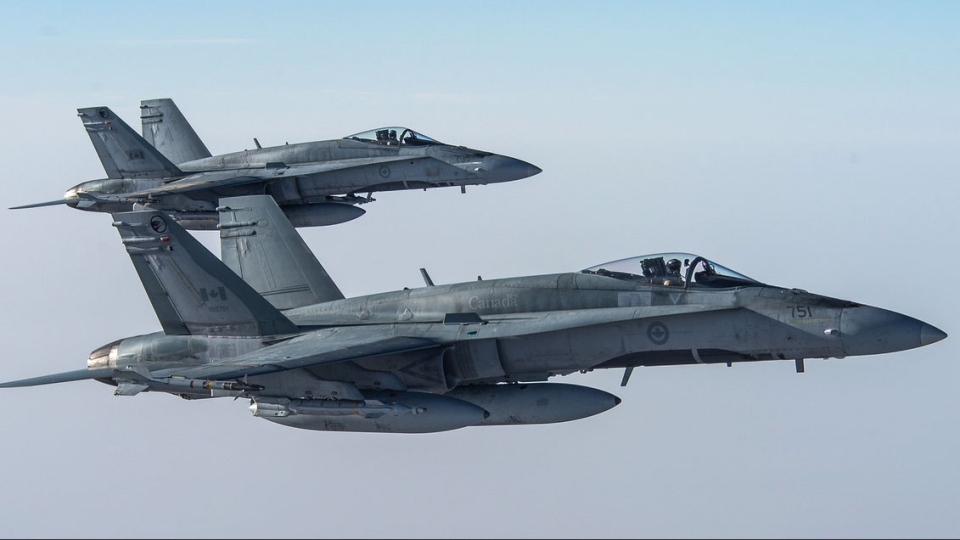 Two CF-18 Hornets prepare to resume their activities after being refueled by a CC-150 Polaris during Operation Impact on Feb. 4, 2015. (Canadian Forces Combat Camera / Department of National Defence)