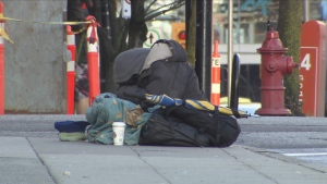 A person sits huddled on a Vancouver sidewalk on March 24, 2015. (CTV)