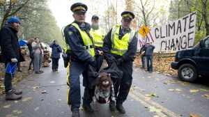 RCMP officers take a protester into custody at an anti-pipeline demonstration in Burnaby, B.C., on Nov. 20, 2014. A civil liberties group says newly disclosed Canadian Security Intelligence Service records on protest surveillance bolster its formal complaint that spies went too far in eyeing environmental activists. (Jonathan Hayward / THE CANADIAN PRESS)