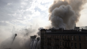 New York City firefighters work the scene of a large fire and a partial building collapse in the East Village neighborhood of New York on Thursday, March 26, 2015. (AP / John Minchillo)