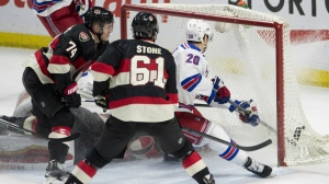 New York Rangers left wing Chris Kreider, right, scores on a bouncing puck under pressure from Ottawa Senators defenceman Mark Borowiecki and right wing Mark Stone during first period NHL action in Ottawa on March 26, 2015. (Adrian Wyld / THE CANADIAN PRESS)