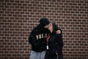 A couple share a kiss as they walks through a snow storm outside the Wells Fargo Center after an NHL hockey game between the Philadelphia Flyers and the Nashville Predators, Saturday, Feb. 21, 2015, in Philadelphia. (AP/Matt Slocum)