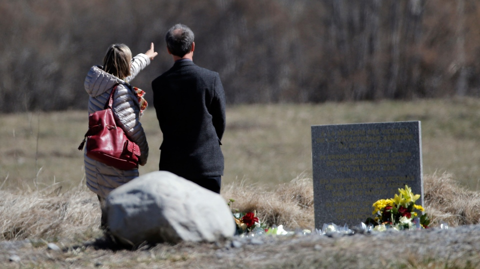 People pay tribute next to a stele and flowers laid in memory of the victims in the area where the Germanwings jetliner crashed in the French Alps, in Le Vernet, France, Friday, March 27, 2015. (AP / Christophe Ena)