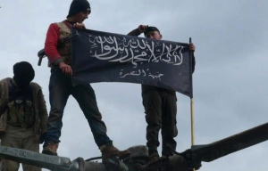 In this Friday, Jan. 11, 2013 file photo, rebels from the Nusra Front wave their brigade flag in Idlib province, northern Syria. (AP / Edlib News Network ENN)