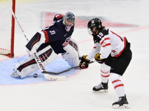 Brianne Jenner, right, of Canada scores the 1-1 equalizer against USA's goalkeeper Jessie Vetter during the 2015 IIHF Ice Hockey Women's World Championship group A match between USA and Canada at Malmo Isstadion in Malmo, southern Sweden, Saturday March 28, 2015. (AP Photo/Claudio Bresciani, TT)