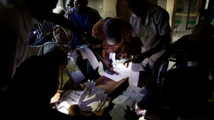 Election officials use the lights from their cellphones to prepare ballots for late voters in one of the polling stations in Kaduna, Nigeria, Saturday, March 28, 2015. (AP / Jerome Delay)