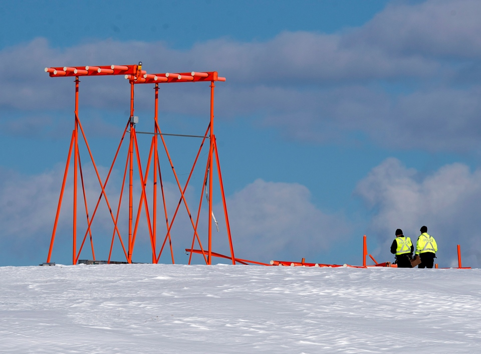 Investigators look at a structure believed to have been hit by Air Canada flight 1AC624 that crashed early Sunday morning during a snowstorm, at Stanfield International Airport in Halifax on Sunday, March 29, 2015.  (THE CANADIAN PRESS/Andrew Vaughan)