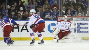 New York Rangers centre Derick Brassard scores against Washington Capitals goalie Braden Holtby during the first period of an NHL hockey game in New York on March 29, 2015. (AP / John Minchillo)