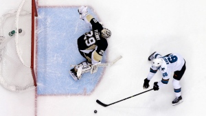 San Jose Sharks' Melker Karlsson (68) can't get a shot off on Pittsburgh Penguins goalie Marc-Andre Fleury (29) during the shootout of an NHL hockey game in Pittsburgh on Sunday, March 29, 2015. (AP / Gene J. Puskar)