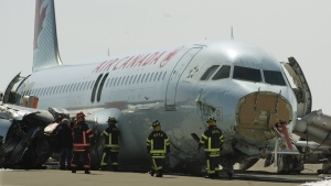 Transportation Safety Board investigators and airport firefighters work at the crash site of Air Canada AC624 that crashed early Sunday morning during a snowstorm, at Stanfield International Airport in Halifax on Monday, March 30, 2015. (Andrew Vaughan / THE CANADIAN PRESS)
