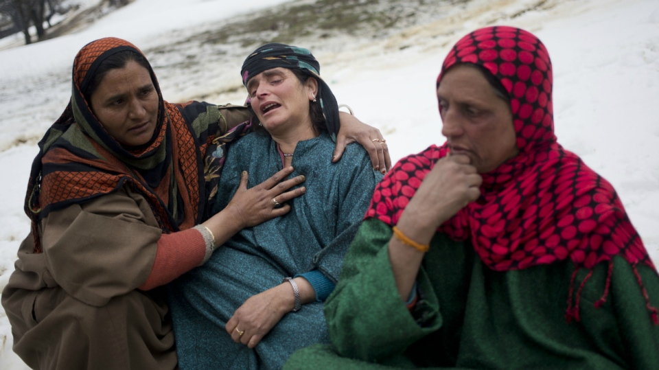 An unidentified woman, left, comforts a relative of landslide victims in the village of Laden some 45 Kilometres west of Srinagar, Indian-controlled Kashmir, Monday, March 30, 2015. (AP / Dar Yasin)