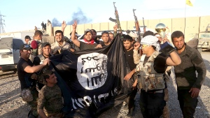 Iraqi security forces and allied Shiite militiamen celebrate as they hold a flag of the Islamic State group they captured in Tikrit, 130 kilometres north of Baghdad, Iraq, Tuesday, March 31, 2015. (AP Photo/Khalid Mohammed)