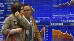 People walk by an electronic stock indicator of a securities firm in Tokyo, Wednesday, April 1, 2015. Asian stock markets were lacklustre Wednesday as China's manufacturing remained weak in February and a Japanese central bank survey showed businesses are wary about the economic outlook. (AP / Shizuo Kambayashi)