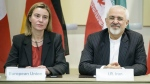 Iranian Foreign Minister Javad Zarif, right, and European Union High Representative Federica Mogherini wait for the start of a meeting on Iran's nuclear program with other officials from Britain, China, France, Germany, Russia and the United States at the Beau Rivage Palace Hotel in Lausanne, Switzerland on March 31, 2015. (AP / Brendan Smialowski)