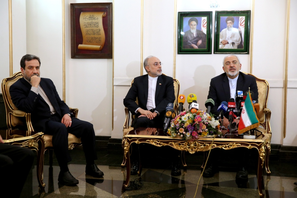 Iranian Foreign Minister Mohammad Javad Zarif, right, speaks with media, as head of Iran's Atomic Energy Organization Ali Akbar Salehi, center, and deputy Foreign Minister Abbas Araghchi listen upon their arrival at the Mehrabad airport in Tehran, Iran, from Lausanne, Switzerland, Friday, April 3, 2015. (AP / Ebrahim Noroozi)
