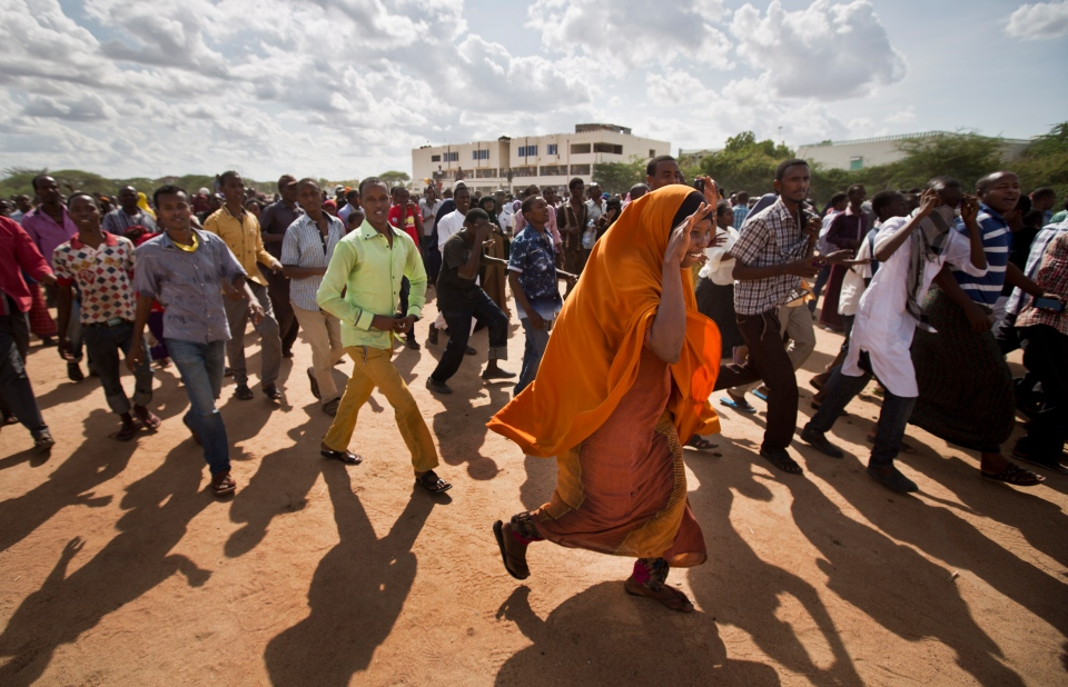 Members of the public run to get a glimpse as authorities display the bodies of the alleged attackers before about 2,000 people in a large open area in central Garissa, Kenya Saturday, April 4, 2015. (AP / Ben Curtis)