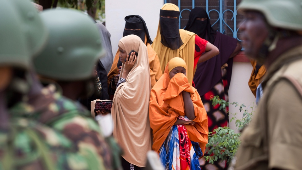 Women look across as Kenya Defence Forces (KDF) soldiers arrive at a hospital to escort the bodies of the attackers to be put on public view, in Garissa, Kenya Saturday, April 4, 2015. (AP / Ben Curtis)