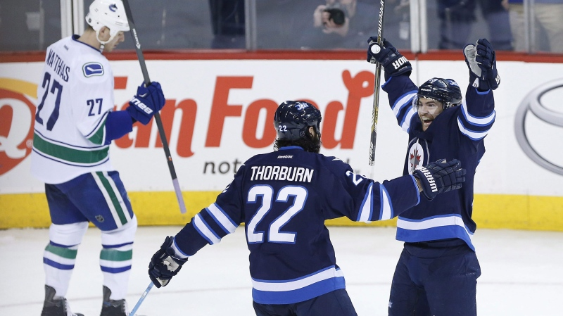 Winnipeg Jets' Chris Thorburn (22) and Jim Slater (19) celebrate Slater's goal against the Vancouver Canucks as Shawn Matthias (27) skates by during first period NHL action in Winnipeg on Saturday, April 4, 2015. THE CANADIAN PRESS/John Woods