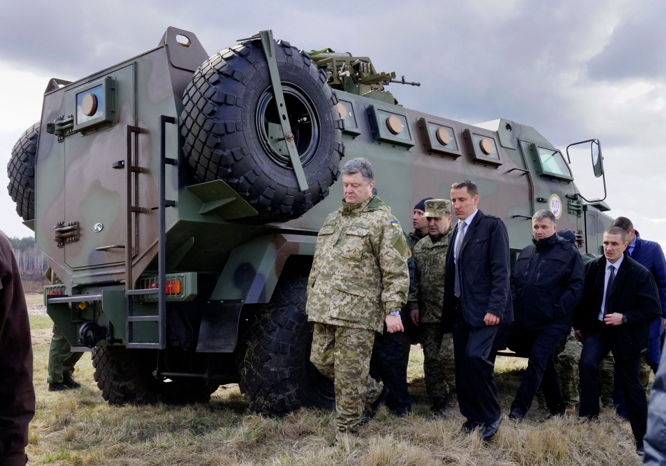 Ukraine's President Petro Poroshenko, left, is followed by officials during presentation of new samples of Ukrainian-made weapons for the Ukrainian Army at a military base in Novi Petrivtsi outside Kyiv, Ukraine on Saturday, April 4, 2015. (AP / Efrem Lukatsky)