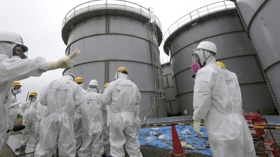 Tokyo Electric Power Co.'s official gives briefing to journalists at H4 tank area, where radioactive water leaked from storage tank in August 2013, at TEPCO's Fukushima Dai-ichi nuclear power plant at Okuma town, Fukushima Prefecture, northeastern Japan, Nov. 7, 2013. (AP / Kimimasa Mayama)