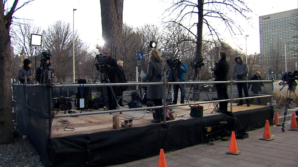 Television journalists speak to their respective broadcast outlets from outside the courthouse on the first day of the Mike Duffy trial in Ottawa, Tuesday, April 7, 2015.