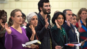 New Canadians take the oath of citizenship in Dartmouth, N.S., on Tuesday, Oct. 14, 2014. (THE CANADIAN PRESS/Andrew Vaughan)